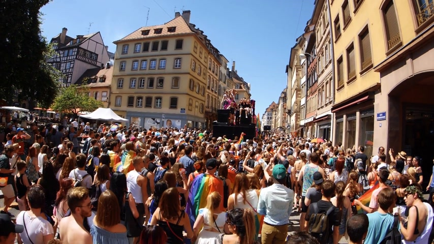 minority group : FRANCE - JUN 10, 2017: Ultrawide French street thousands people jumping dancing gay supporters with rainbow flag slow motion Lesbian Gay Bisexual Transgender LGBT GLBT visibility march pride FestiGays Stock Footage