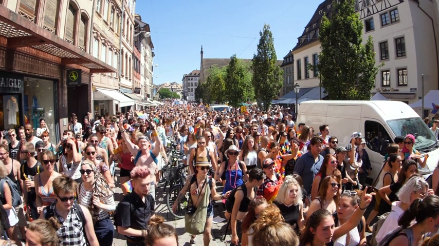 párok : STRASBOURG, FRANCE - JUN 10, 2017: View from above French street with thousands of people jumping dancing gay supporters dancing with rainbow flag in slow motion LGBT GLBT visibility march pride Stock mozgókép