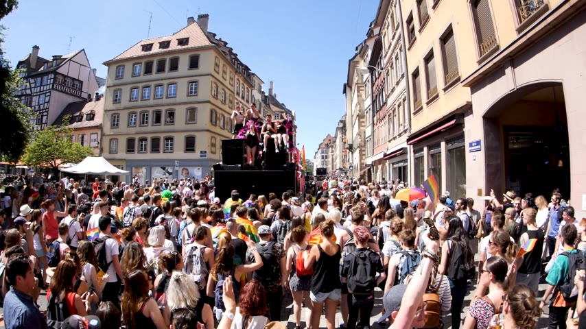 гордый : FRANCE - JUN 10, 2017: Happy atmosphere on French street thousands people jumping dancing gay supporters with rainbow flag slow motion Lesbian Gay Bisexual Transgender LGBT visibility march pride