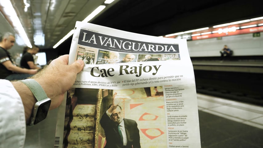 asal : BARCELONA - JUNE 1 2018: POV man reading in Barcelona Metro station the La Vanguardia newspaper cover Cae Rajoy translated as Mariano Rajoy fall when a vote of no confidence ousted his government