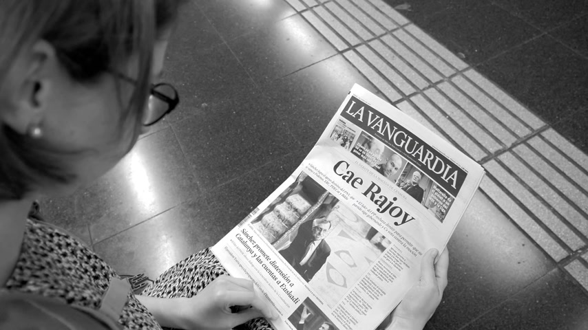 former : BARCELONA, SPAIN - JUNE 1 2018: Woman reading in Barcelona Metro station the La Vanguardia newspaper cover Cae Rajoy translated as Mariano Rajoy fall when a vote of no confidence ousted his government