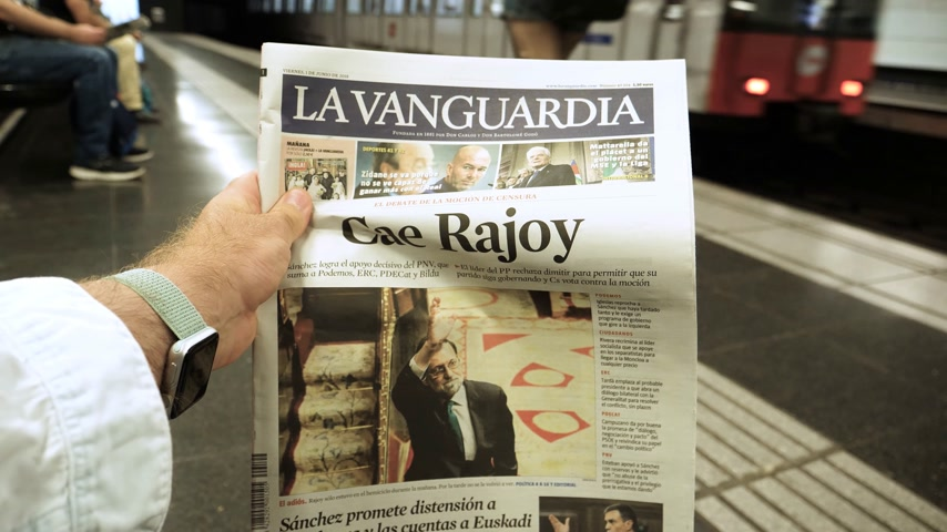 newspaper cover : BARCELONA - JUNE 1 2018: Man hand Barcelona Metro station the La Vanguardia newspaper cover Cae Rajoy translated as Mariano Rajoy fall when a vote of no confidence ousted his government POV