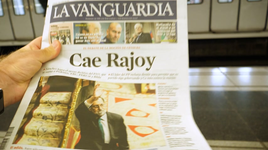 asal : BARCELONA, SPAIN - JUNE 1 2018: Man reading in Barcelona Metro station the La Vanguardia newspaper cover Cae Rajoy translated as Mariano Rajoy fall when a vote of no confidence ousted his government