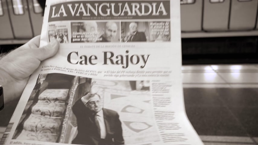 başkan : BARCELONA, SPAIN - JUNE 1 2018: Man reading in Barcelona Metro station the La Vanguardia newspaper cover Cae Rajoy translated as Mariano Rajoy fall black and white Stok Video