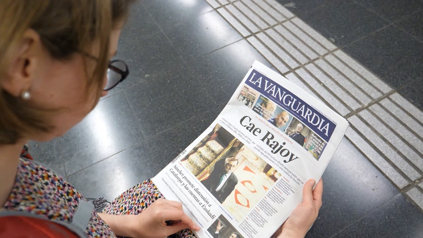 newspaper cover : BARCELONA, SPAIN - JUNE 1 2018: Curious woman reading in Barcelona Metro station La Vanguardia newspaper cover Cae Rajoy translated Mariano Rajoy fall when vote of no confidence ousted his government