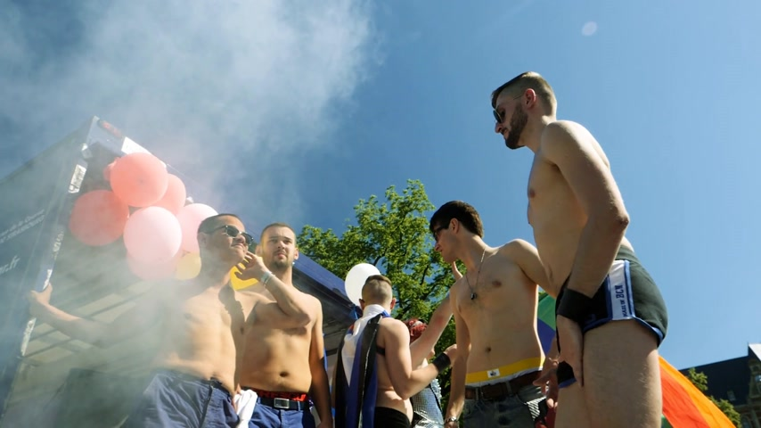 lesbian couple : STRASBOURG, FRANCE - JUN 10, 2017: Group excited gay men people dancing in slow motion with rainbow flag behind at Lesbian Gay Bisexual Transgender LGBT visibility march pride smoke grenade