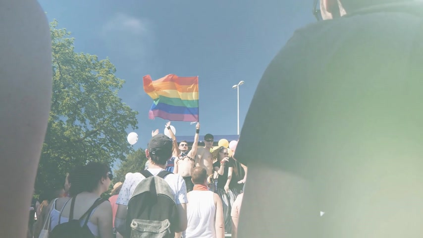 minority group : STRASBOURG, FRANCE - JUN 10, 2017: Sunlight flare over friends gay people supporters dancing with rainbow flag in slow motion at Lesbian Gay Bisexual Transgender LGBT GLBT visibility march pride FestiGays -