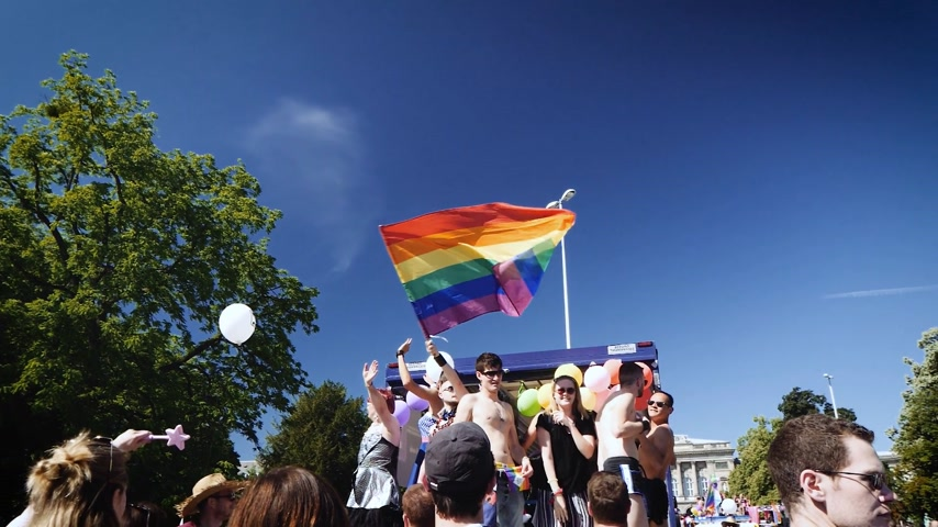 gururlu : STRASBOURG, FRANCE - JUN 10, 2017: Cinematic slow motion of majestic gay flag waving as gay friends are dancing on truck during gay pride in France, Strasbourg - annual LGBT pride FestiGays