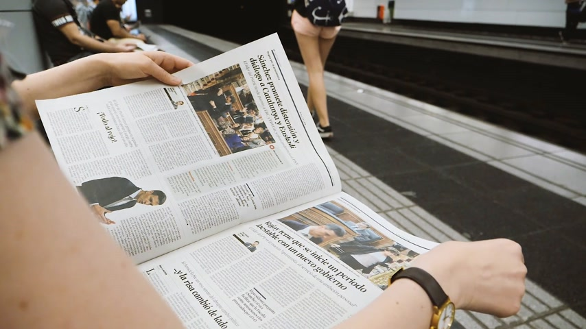 hlasování : BARCELONA - JUNE 1 2018: Woman reading in Barcelona Metro station the La Vanguardia newspaper with portrait article about Pedro Sanchez Spains new prime minister slow motion