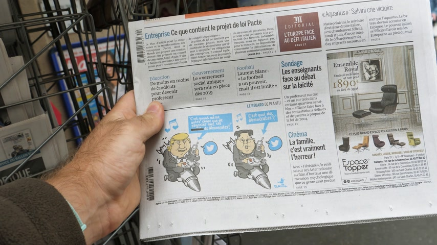 caricatura : PARIS, FRANCE - JUNE 13, 2018: Man buying Monde newspaper at press kiosk showing on cover caricature of U.S. President Donald Trump meeting North Korean leader Kim Jong-un in Singapore