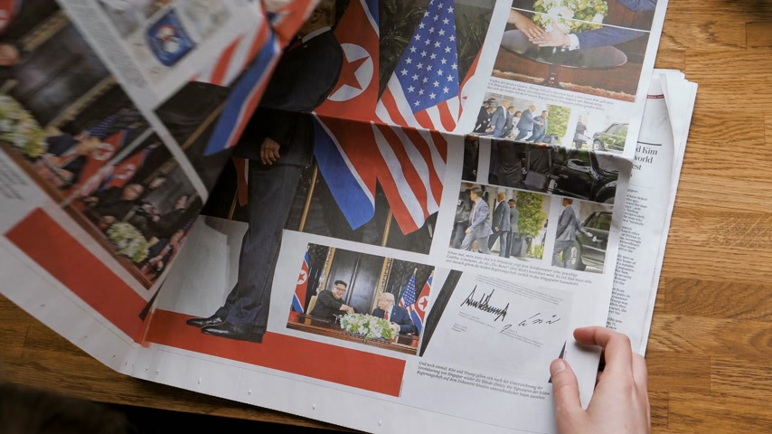 diário : PARIS, FRANCE - JUNE 13, 2018: Woman reading German Die Welt newspaper in the office with U.S. President Donald Trump meeting North Korean leader Kim Jong-un in Singapore politics