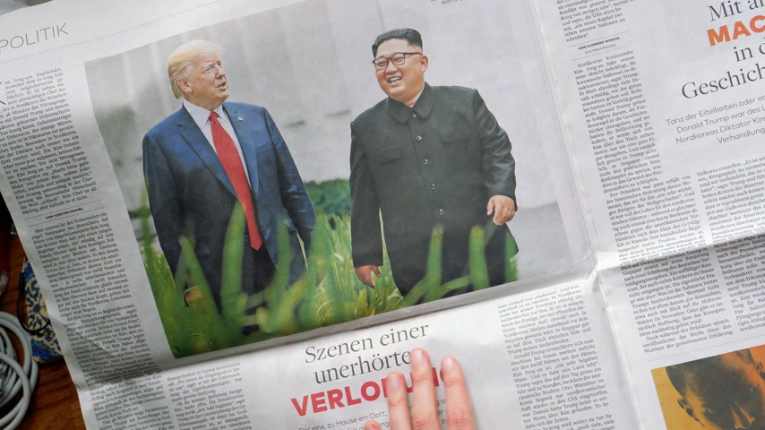 donald trump : PARIS, FRANCE - JUNE 13, 2018: Woman reading German Die Welt newspaper in the office showing on U.S. President Donald Trump meeting North Korean leader Kim Jong-un in Singapore