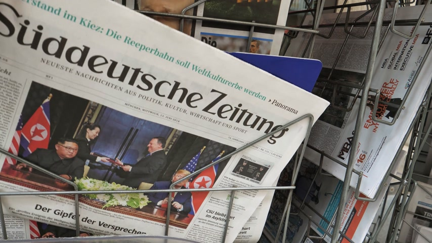 abonament : PARIS, FRANCE - JUNE 13, 2018: Holding German Suddeutsche Zeitung on stand newspaper at press kiosk showing on cover  U.S. President Donald Trump meeting North Korean leader Kim Jong-un in Singapore