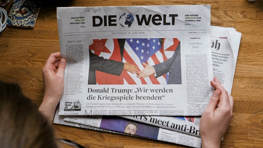 buy newspaper : PARIS, FRANCE - JUNE 13, 2018: Woman reading German Die Welt newspaper in the office showing on cover  U.S. President Donald Trump meeting North Korean leader Kim Jong-un in Singapore Stock Footage