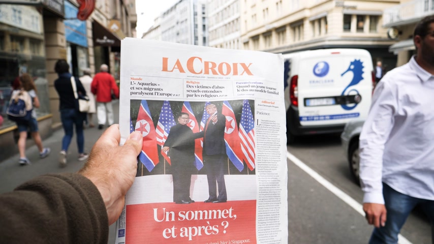 buy newspaper : PARIS, FRANCE - JUNE 13, 2018: Man buying La Croix newspaper at press kiosk showing on cover U.S. President Donald Trump meeting North Korean leader Kim Jong-un in Singapore - slow motion Stock Footage