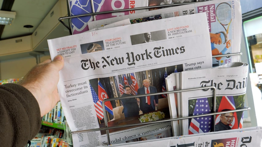 donald trump : PARIS, FRANCE - JUNE 13, 2018: The New York Times on stand newspaper at press kiosk showing on cover  U.S. President Donald Trump meeting North Korean leader Kim Jong-un in Singapore - woman walking slow motion Stock Footage