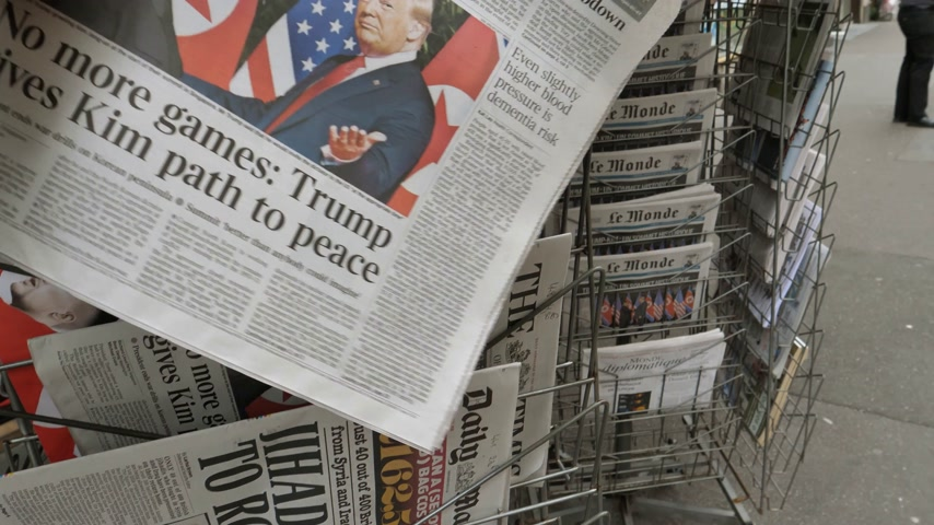 buy newspaper : PARIS, FRANCE - JUNE 13, 2018: Man buying The Times newspaper at press kiosk cover U.S. President Donald Trump meeting North Korean leader Kim Jong-un in Singapore