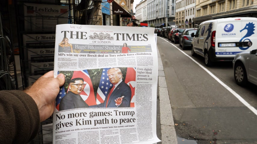 buy newspaper : PARIS, FRANCE - JUNE 13, 2018: Man showing in slow motion The Times newspaper at press kiosk showing on cover  U.S. President Donald Trump meeting North Korean leader Kim Jong-un in Singapore