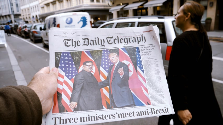 buy newspaper : PARIS, FRANCE - JUNE 13, 2018: Man buying The Daily Telegraph newspaper at press kiosk showing on cover U.S. President Donald Trump meeting North Korean leader Kim Jong-un in Singapore slow motion