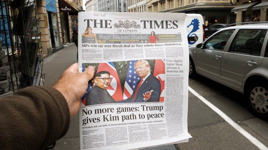 times : PARIS, FRANCE - JUNE 13, 2018: Slow motion man buying The Times newspaper at press kiosk showing on cover  U.S. President Donald Trump meeting North Korean leader Kim Jong-un in Singapore