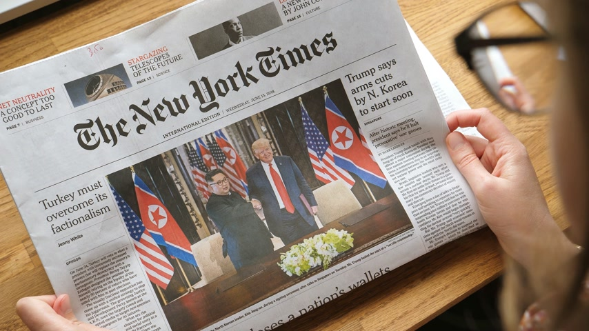 donald trump : PARIS, FRANCE - JUNE 13, 2018: Woman reading The New York Times newspaper in the office showing on cover  U.S. President Donald Trump meeting North Korean leader Kim Jong-un in Singapore