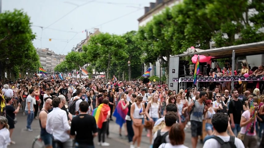 minority group : STRASBOURG, FRANCE - JUN 10, 2017: Gay pride shot with tilt-shift lens used at LGBT parade with thousands of people dancing on the street - elevated view Stock Footage