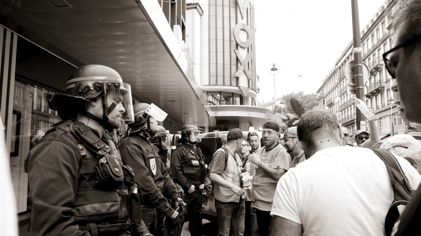syndicate : STRASBOURG, FRANCE - JUN 20, 2018: Police officer surveillance of SNCF French train worker demonstration strike protest against Macron French government string reforms - slow motion, black and white
