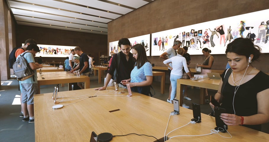 face id : PARIS, FRANCE - CIRCA 2018: Woman comparing iPhone telephone smartphones in Apple store with couple nearby deciding which phone to buy Stock Footage
