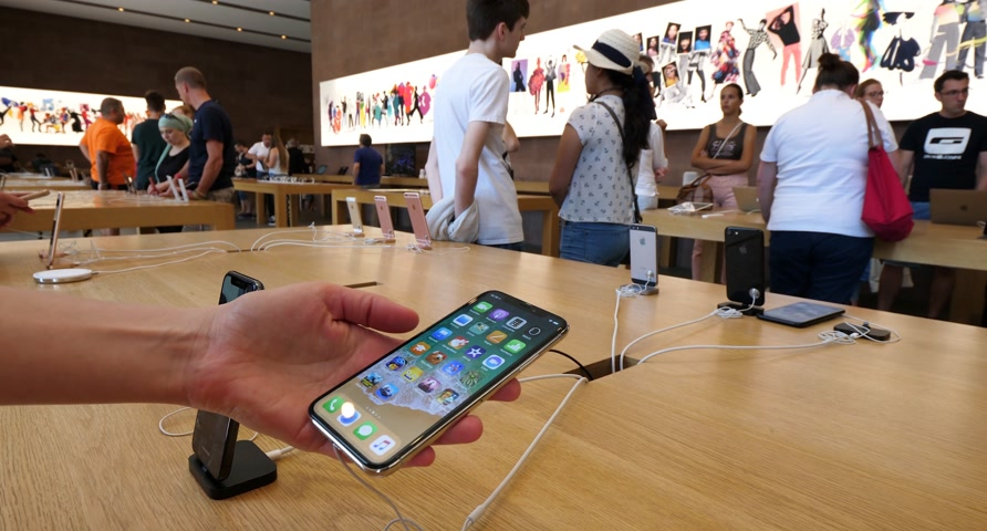 jel : PARIS, FRANCE - CIRCA 2018: Woman using in Apple store the latest new Apple iPhone X 10 smartphone with customers walking around choosing the best tech Stock mozgókép