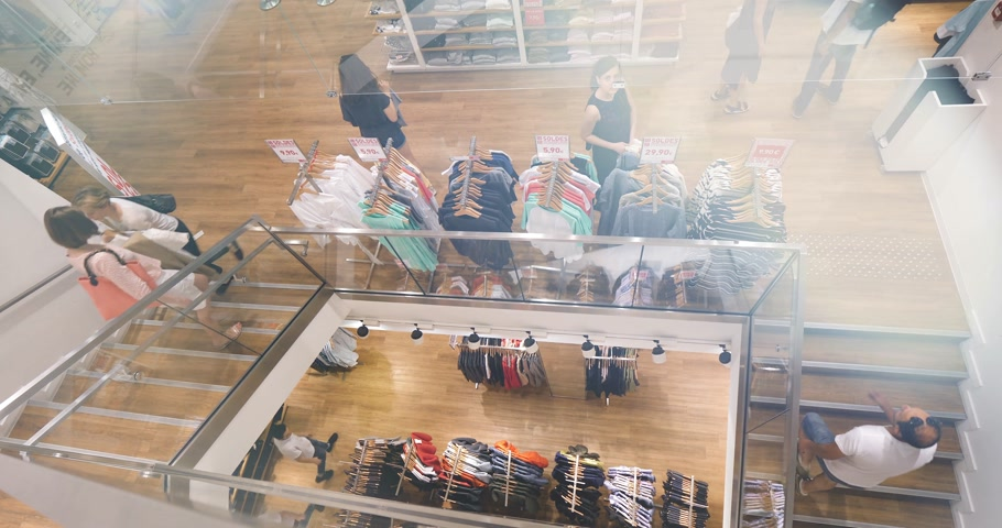 botas : PARIS, FRANCE - CIRCA 2018: Uniqlo fashion store in France with French fashionista people woman walking the store for Japanese fashion and ready-to-wear - view from above with a magnificent drone angle