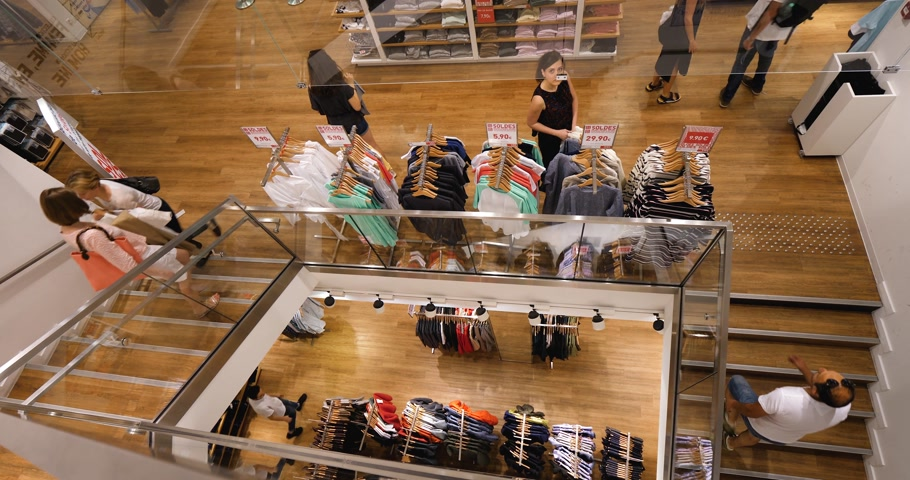uniqlo : PARIS, FRANCE - CIRCA 2018: Uniqlo fashion store in France with French fashionista people woman walking the store for Japanese fashion and ready-to-wear - view from above with a magnificent drone angle