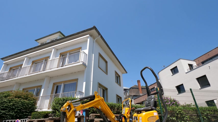 wheel loader : STRASBOURG, FRANCE - JUN 30, 2018: Wide angle of Small yellow excavator tractor rented from Kiloutou in front of the newly constructed apartment building in France Stock Footage