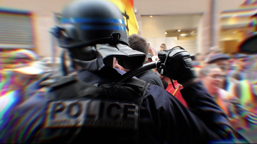 asa : STRASBOURG, FRANCE - JUN 20, 2018: Cinematic focus on the rear of police officer with mask ready to use the police bat rubber baton, security truncheons against protesters people