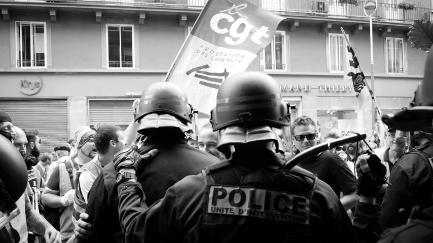 asa : STRASBOURG, FRANCE - JUN 20, 2018: Slow motion with police officer ready to protect with rubber bat from the SNCF French demonstration strike protest against Macron French government string of reforms