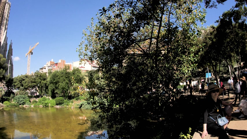 Гауди : BARCELONA, SPAIN - CIRCA 2018: Pan to Sagrada Familia Church built by Antoni Gaudi from Chinese tourists taking photos selfies with the magnificent religious architecture from the Place de Gaudi