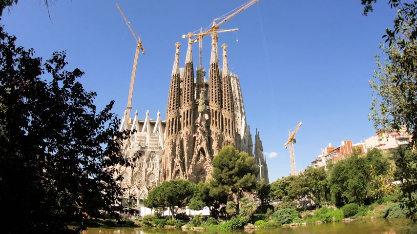 establishment : Cinematic Sagrada Familia Church built by Antoni Gaudi - cranes construction over the towers of the majestic cathedral