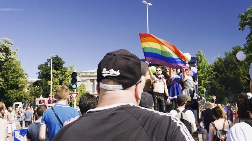 minority group : STRASBOURG, FRANCE - JUN 10, 2017: Man waving gay pride flag with Strasbourg University in the aground during gay pride parade- Stock Footage