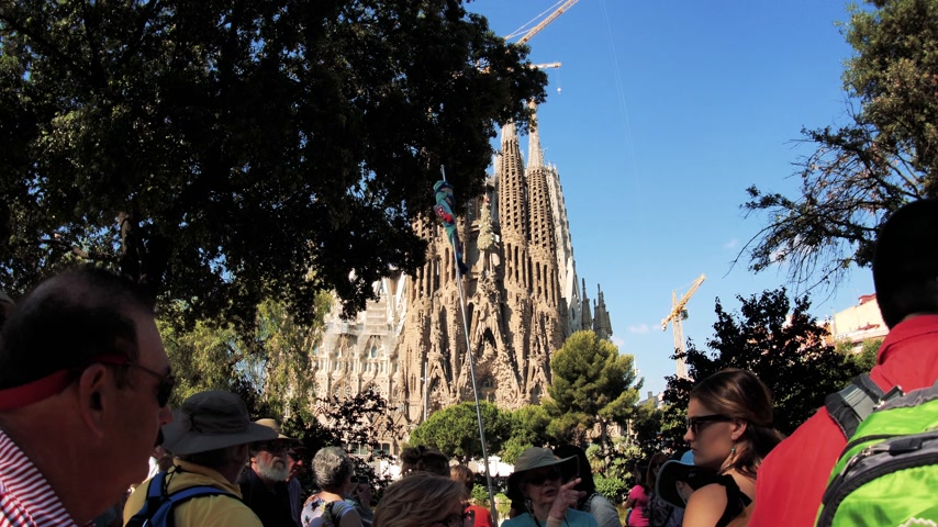 establishment : BARCELONA, SPAIN - CIRCA 2018: Tourist group admiring taking photos of Sagrada Familia Church built by Antoni Gaudi from the Placa de Gaudi suring summer holidays