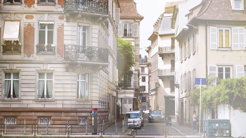 water taxi : STRASBOURG, FRANCE - CIRCA 2018: Sunlight flare over Cinematic 4k UHD footage of  Rue des Ecrivains Writers street in central Strasbourg with pedestrians, locals and tourists and Mercedes Benz taxi car