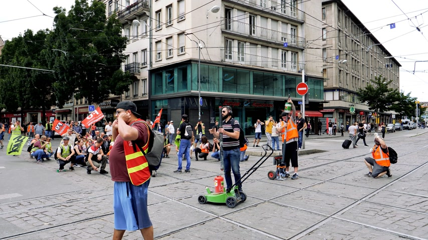 syndicate : STRASBOURG, FRANCE - JUN 20, 2018: SNCF French train worker preparing to detonate acoustic noise bomb at demonstration strike protest against Macron French government string of reforms