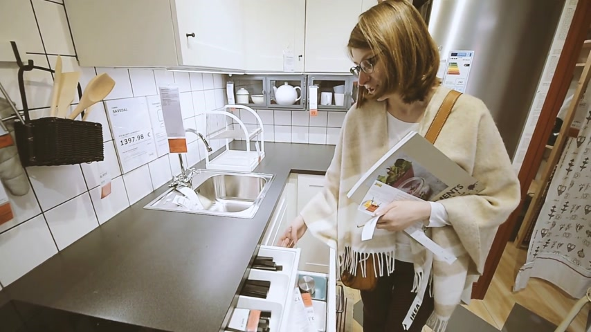 cabinet : PARIS, FRANCE - CIRCA 2018: Woman selecting the kitchen accesories inside IKEA furniture warehouse store