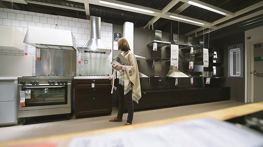 ikea : PARIS, FRANCE - CIRCA 2018: Admiring kitchen hoods, ovens, hobs inside modern IKEA furniture store browsing through diverse furniture, decoration warehouse goods - wide angle