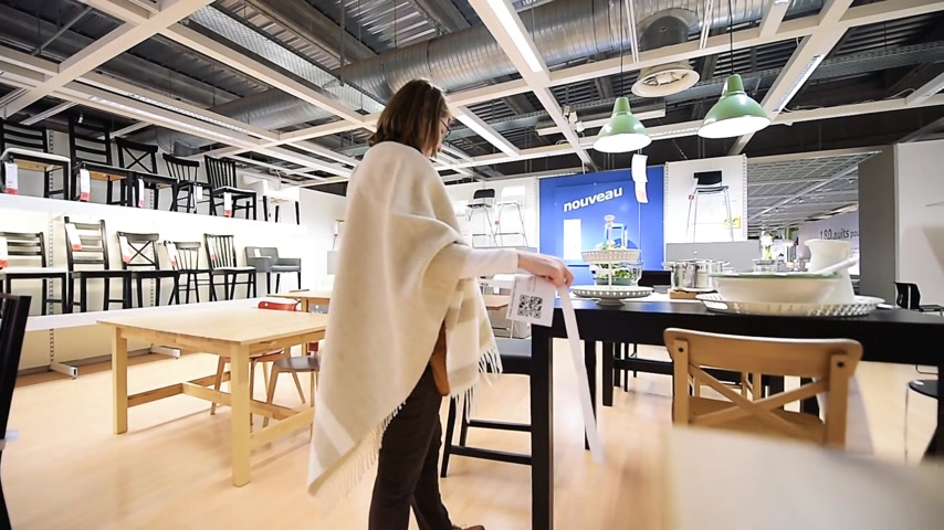 ikea : PARIS, FRANCE - CIRCA 2018: Wide view of interior of IKEA furniture store with woman customer browsing multiple tables and chairs