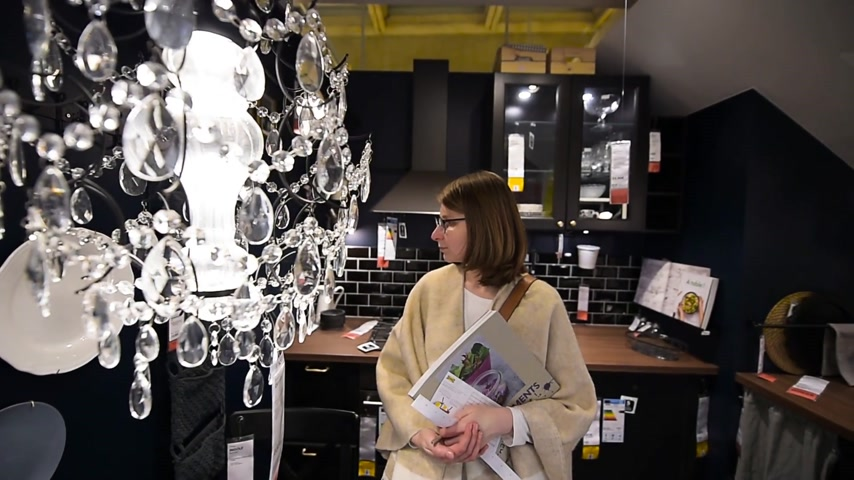 ikea : PARIS, FRANCE - CIRCA 2018: Woman admiring the modern kitchen furniture with impressive Chrystal chandelier inside IKEA furniture store