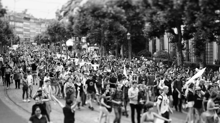 minority group : STRASBOURG, FRANCE - JUN 10, 2017: Black and white of tilt-shift lens focusing used at LGBT gay pride parade with thousands of people dancing on the street - elevated view
