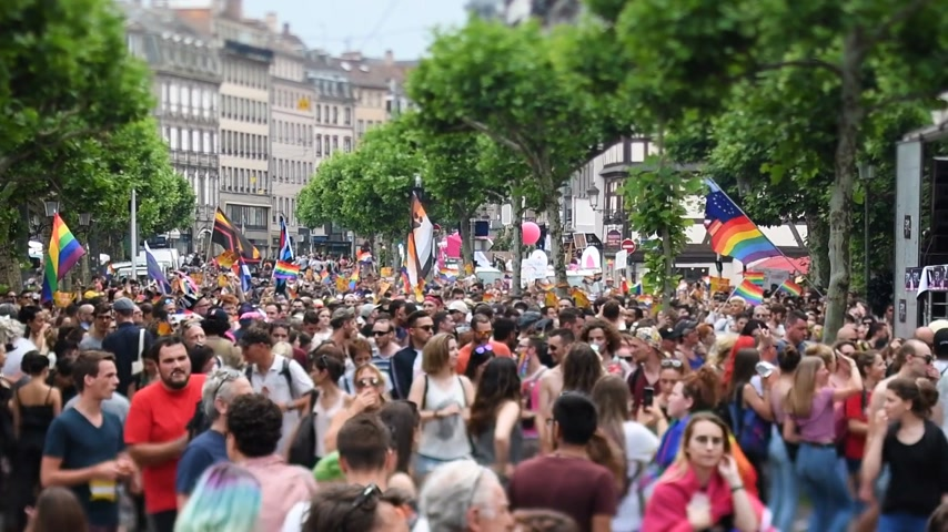 tilt shift : STRASBOURG, FRANCE - JUN 10, 2017: Large crowd of cinematic tilt-shift lens at LGBT gay pride parade with thousands of people dancing on the street - elevated view Stock Footage
