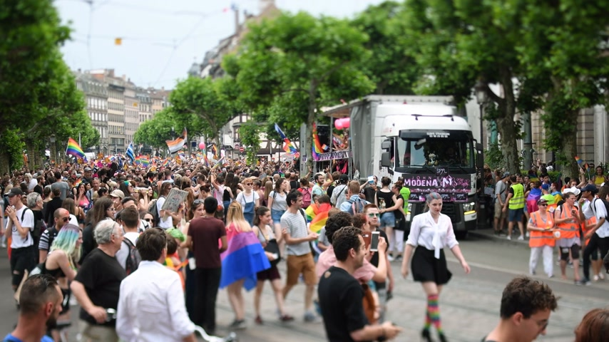 minority group : STRASBOURG, FRANCE - JUN 10, 2017: Large crowd waving LGBT flags at gay pride parade with thousands of people dancing on the street - elevated view with gay truck