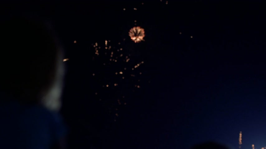 firework display : Loop reverse footage of unrecognizable silhouette of a people watching multiple explosions in red yellow blue colors - cinematic 4k footage implosion Stock Footage