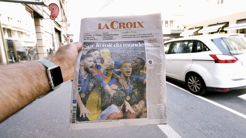 él : PARIS, FRANCE - JUL 16, 2018: Man reading La Croix newspaper announcing France champion title after French national football team won their FIFA World Cup 2018 final game on the roof of the world slow motion
