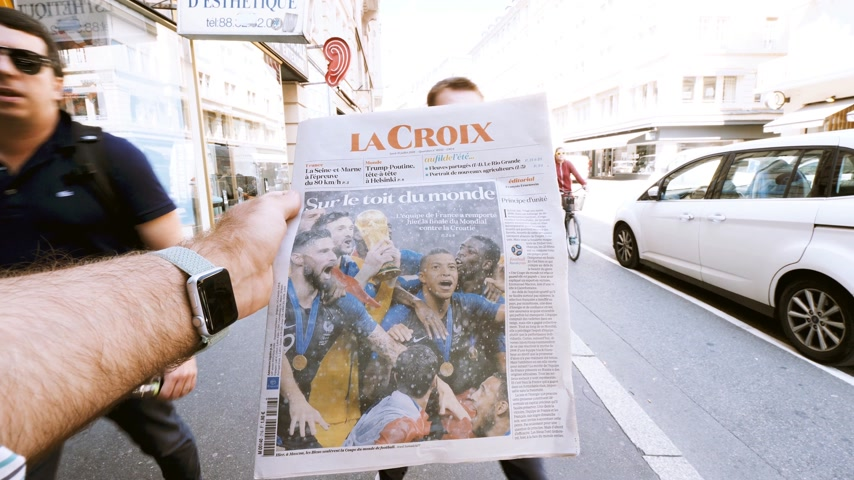 el : PARIS, FRANCE - JUL 16, 2018: Slow motion man reading La Croix newspaper announcing France champion title after French national football team won their FIFA World Cup 2018 final game on the roof of the world